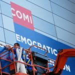 A completely legal Mexican-American convention worker removes signage from the Time Warner Cable Arena Monday afternoon - (AP Photo)